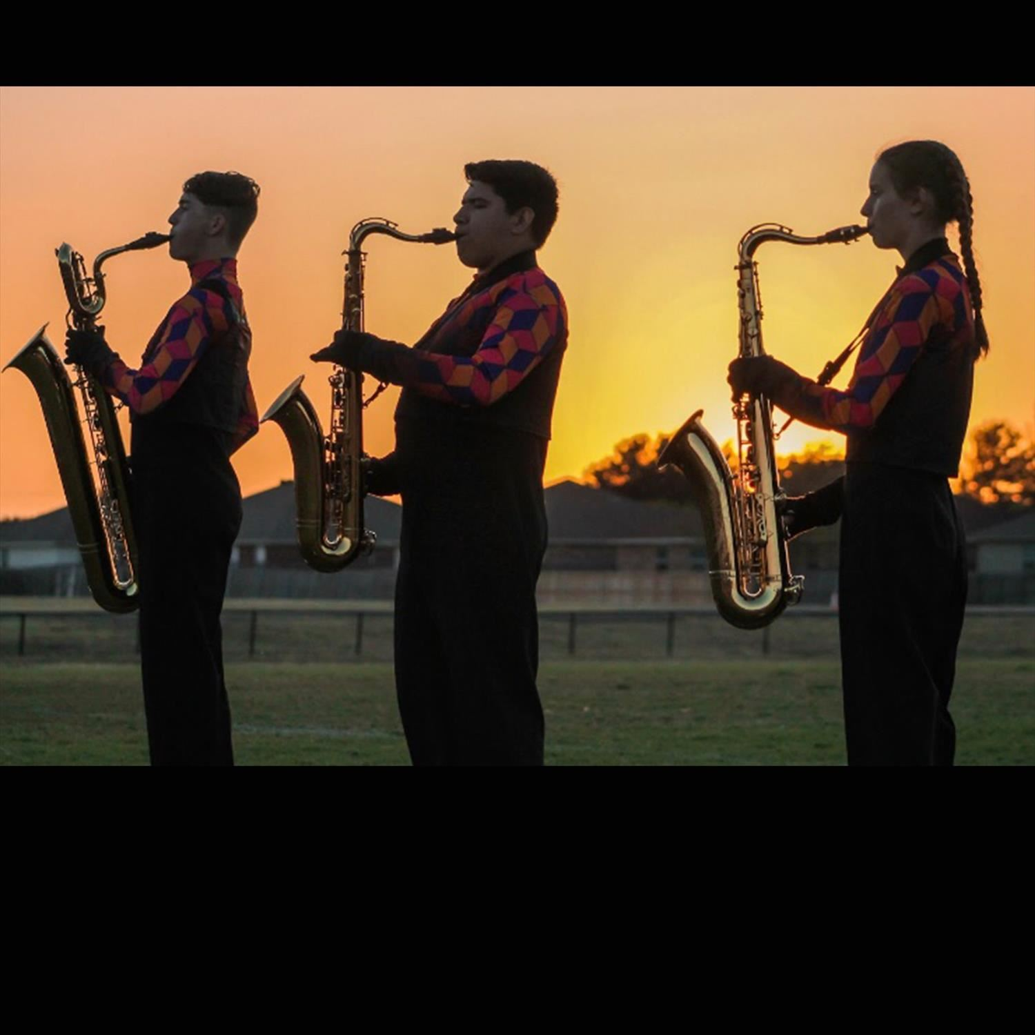 Students playing instruments with setting sun behind
