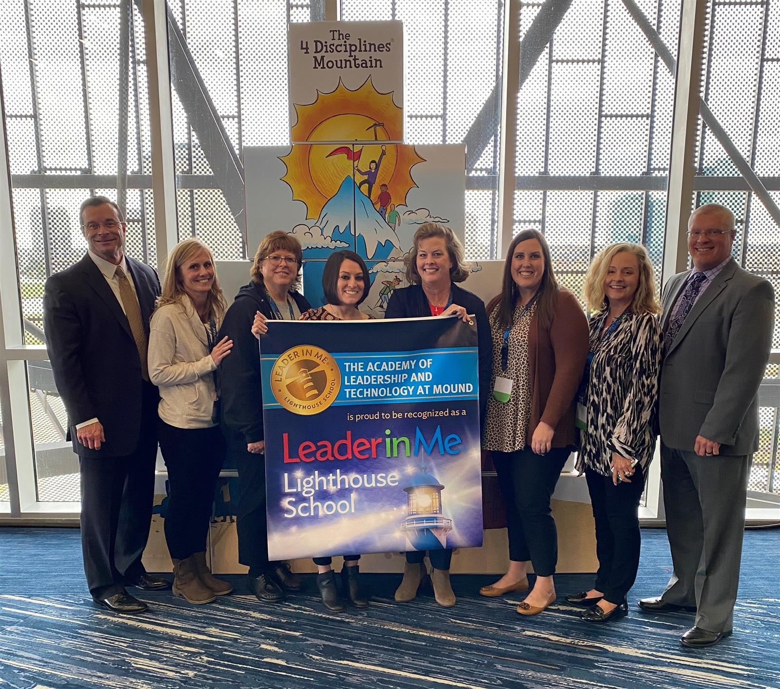 School and District Leaders holding Leader In Me Banner